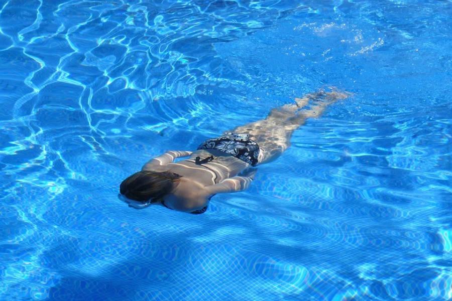 Chica nadando en piscina